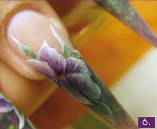 Ugyanezzel az eljárással leveleket is festhetünk a virágaink köré, én erre világos zöldként a 906 és a Giga fehér, sötét színként a 906 és a 010-es zselék keverékét használtam, a levelek szélét pedig ugyancsak Giga fehérrel világosítottam. Végül a virágok belső és külső részét is akrilfestékkel emelem ki, festhetünk Giga sárgával bibéket is. A Top Shine kötése után apró pöttyökkel egészítettem még ki.